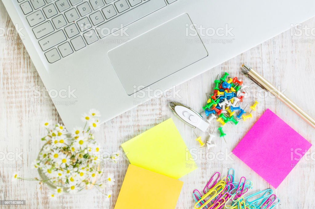 Work Desk With Laptop Computer Office Supplies and Flowers stock photo