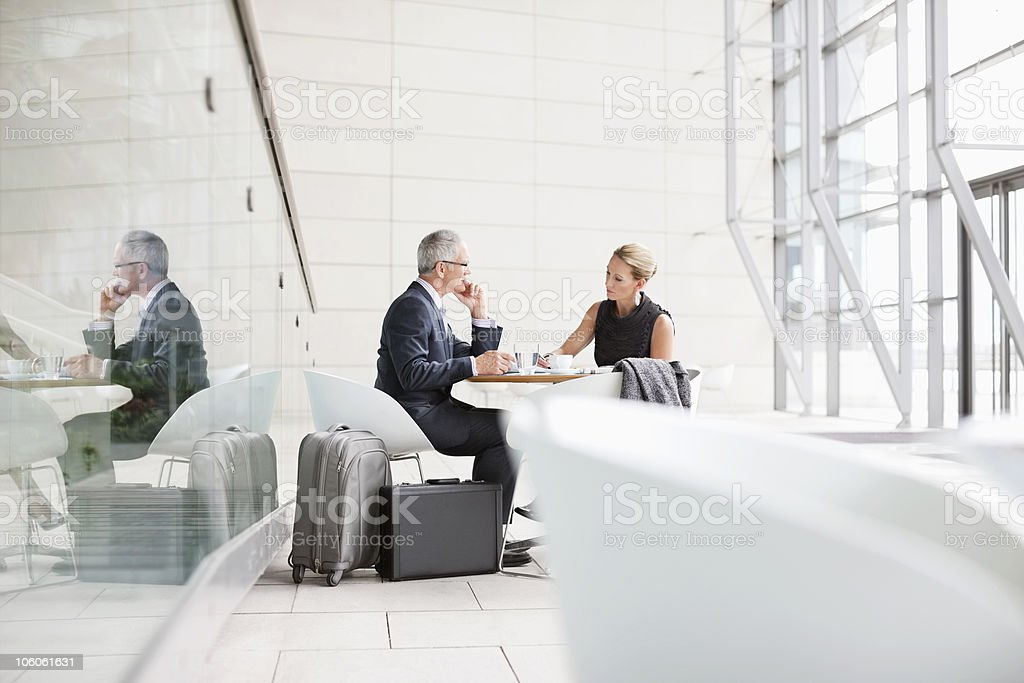Work discussion between two business person with luggage around royalty-free stock photo