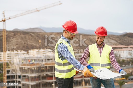istock Work engineers discussing about new building area - Young builders reading the project in the construction site - Carpentry teamwork engineering concept 1321196786