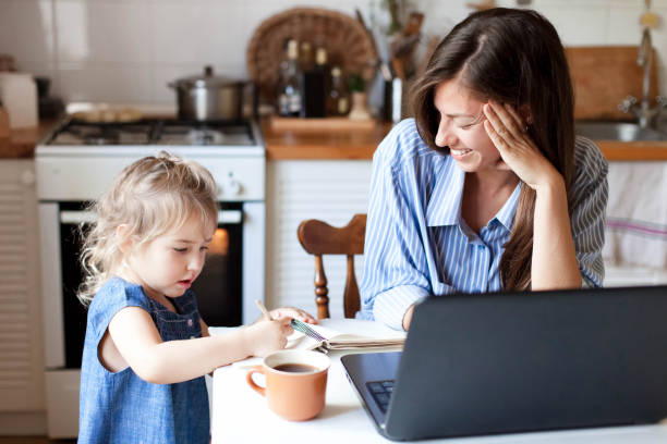 Work from home office with kid. Working mother using laptop. Cozy freelance workplace at kitchen table. stock photo