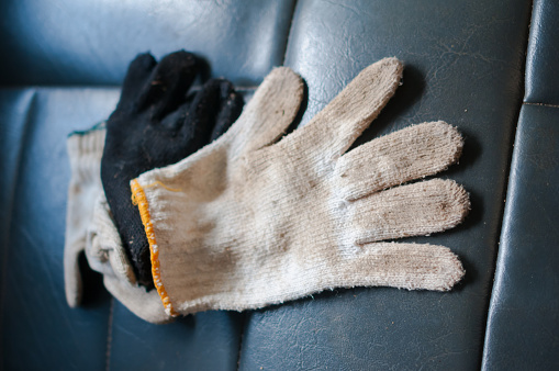 Work gloves on a leather background.
