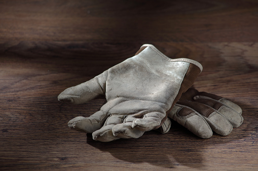 A pair of work gloves on a wood surface with window light