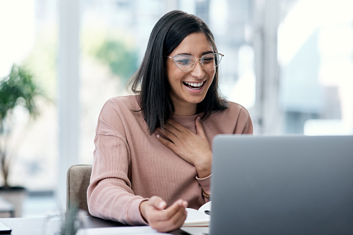 Shot of a young woman using a laptop and looking surprised while working from home