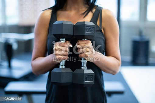 Unrecognizable woman exercising with dumbbells in the gym
