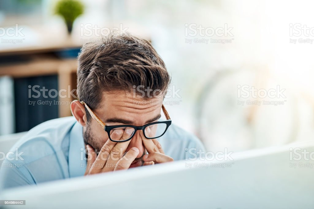 Work has it's days Shot of a young businessman suffering with a headache while working in an office 30-39 Years Stock Photo