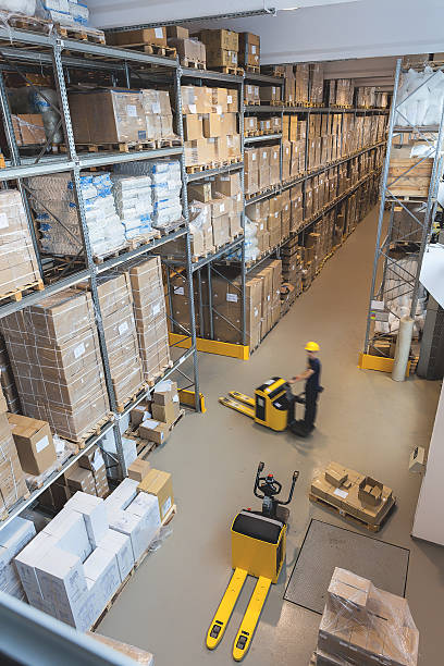 Work in a warehouse Products on a metal stillage, pallet trucks and a workers pallet jack stock pictures, royalty-free photos & images