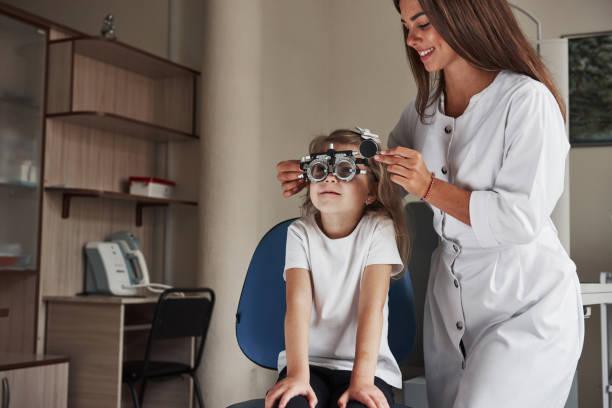 Arbeiten in Arbeit. Kleines Mädchen in Gläsern in der Klinik sitzen und ihre Augen testen lassen – Foto