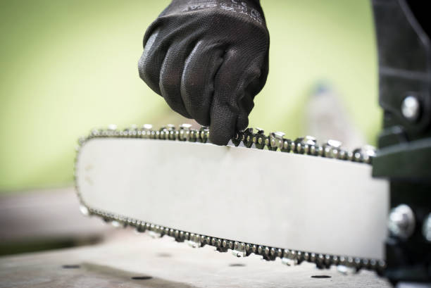 Trabajo en el taller, cambio de la cadena en la motosierra - foto de stock