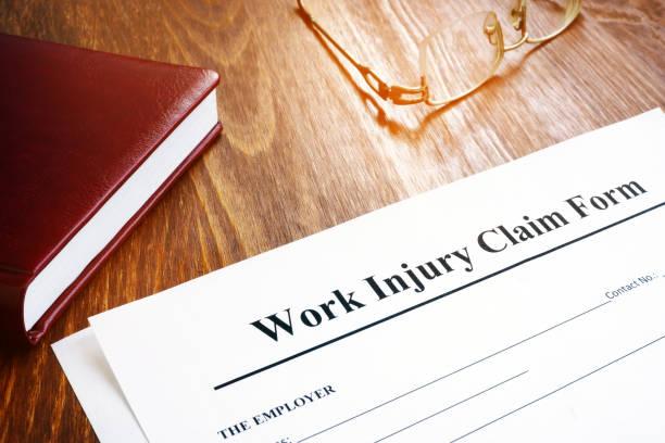 work injury claim form and glasses on desk. - soddisfazione foto e immagini stock
