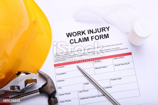 Work Injury Claim Form next to some tools and protective helmet  (Form created specifically for this shot)  - Selective Focus -