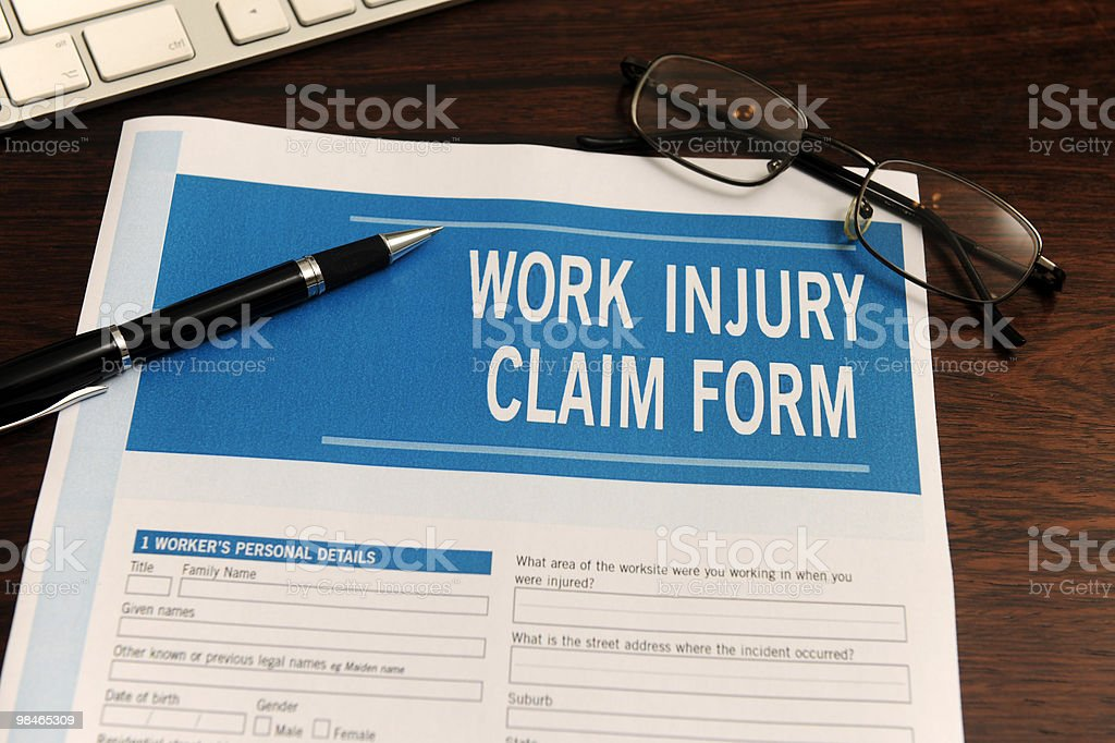 Work injury claim form with pen and glasses royalty-free stock photo