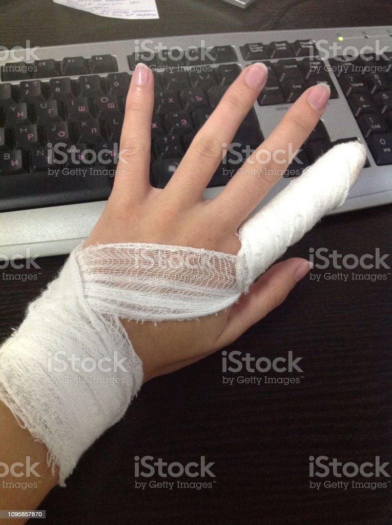 Work injury. Female hand with a bandaged finger on the background of...