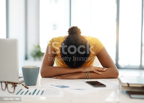 Shot of a young businesswoman with her head down on her office desk