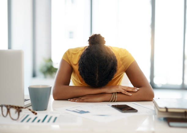 Work is making her miserable Shot of a young businesswoman with her head down on her office desk mental burnout stock pictures, royalty-free photos & images