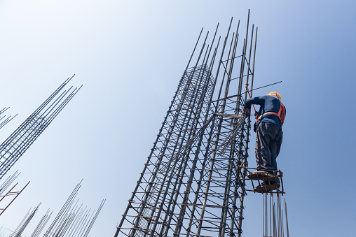 worker at altitude strengthens the pillars from rebar, on the blue sky background. candid, real people