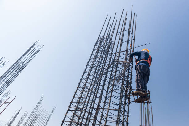 work knits fittings worker at altitude strengthens the pillars from rebar, on the blue sky background. candid, real people rod stock pictures, royalty-free photos & images