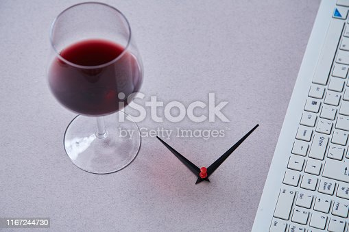 1175869940istockphoto Work life balance choice concept. Arrows pointing to a computer keyboard and a glass of wine. 1167244730