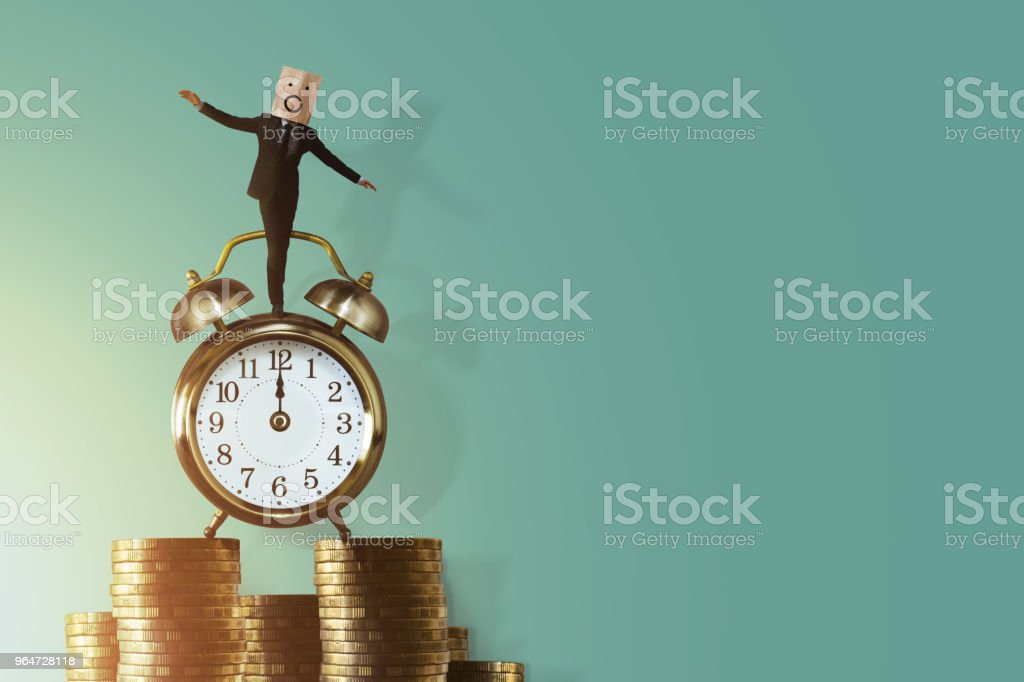 Work Life Balance for Time and Money Concept. Excited Businessman Balancing his body on Vintage Alarm Clock and Stack of Coin. Face Covered by paper Bag with Cartoon Emotion royalty-free stock photo