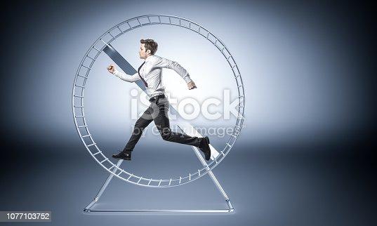 young businessman run in huge hamster wheele