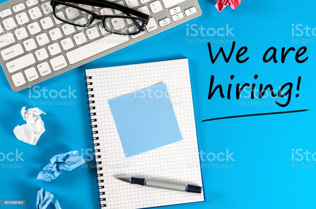 Work notepad, keyboard and glasses on blue desk with text We're Hiring stock photo