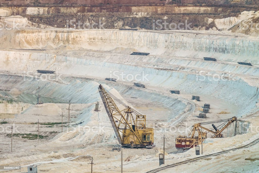 Work of heavy grapple excavators in a deep chalk quarry. Mining industry. Big clamshell excavators in the lowland quarry. stock photo