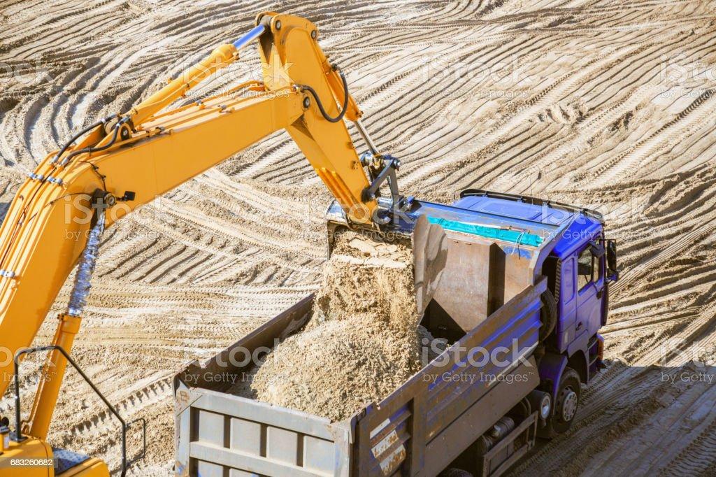 在採石場挖掘機的工作。正在載入砂。 免版稅 stock photo