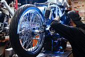 Welder in protective mask repairing custom bike