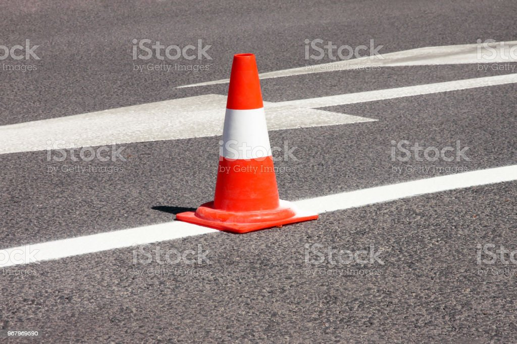 Work on road. Construction cone. Traffic cone, with white and orange stripes on asphalt. Street and traffic signs for signaling. Road maintenance, under construction sign and traffic cone on road. stock photo