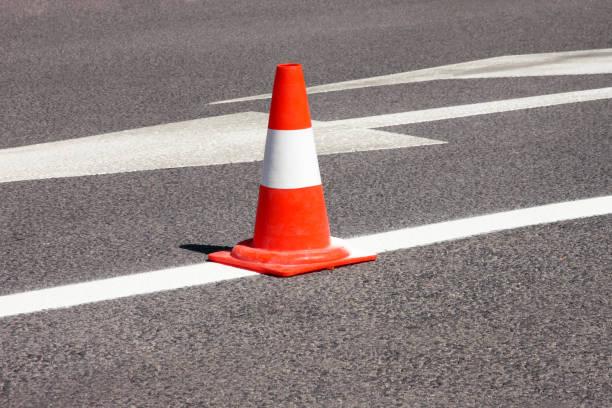 Trabalhar na estrada. Cone de construção. Cone de tráfego, com listras brancas e laranja no asfalto. Sinais de rua e tráfego para sinalização. Manutenção de estradas, sob o cone de tráfego e sinal de construção na estrada. - foto de acervo