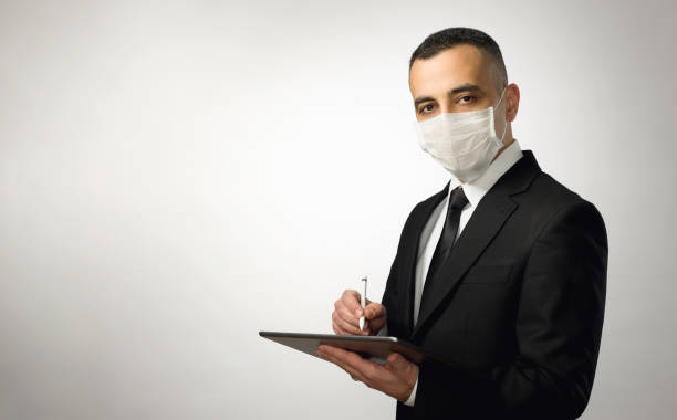 Work Online Concept,  Businessman With Mask Holding Digital Tablet, Available Copy Space stock photo