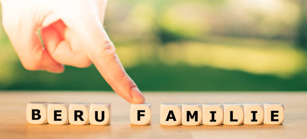 """Work or family? A finger pushes the letter F away from the German word """"Beruf"""" (""""work"""") towards the word """"Familie"""" (""""family""""). A symbol for work life balance. stock photo"""