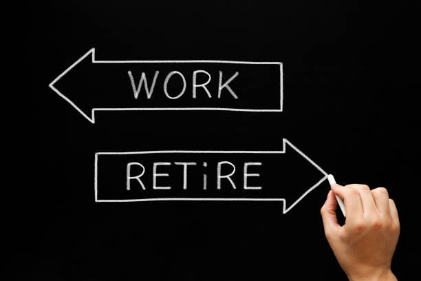 Work Or Retire Decision Arrows Concept Hand writing Work and Retire on two arrows with chalk on blackboard. Concept about the decision making of an aging worker between continue working or entering retirement. 401k stock pictures, royalty-free photos & images