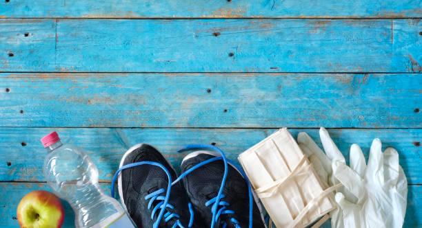 in Zeiten des Coronavirus trainieren; Maske, medizinische Handschuhe, Paar Läufer, Wasser, Apfel, Konzept – Foto