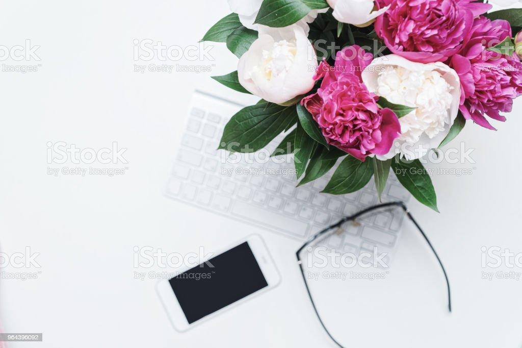 Werkplek mobiele telefoon toetsenbord bril roze pioen - Royalty-free Bedrijfsleven Stockfoto