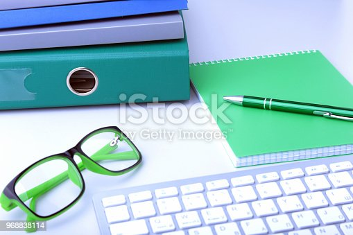 istock Work place table with folders file on it and modern laptop, pen, glasses and textbook lying near on a white background. 968838114