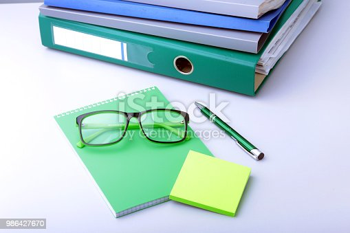 istock Work place table with folders file on it and modern laptop, pen, glasses and textbook lying near on a white background. 986427670