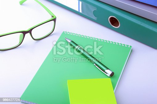 istock Work place table with folders file on it and modern laptop, pen, glasses and textbook lying near on a white background. 986427724