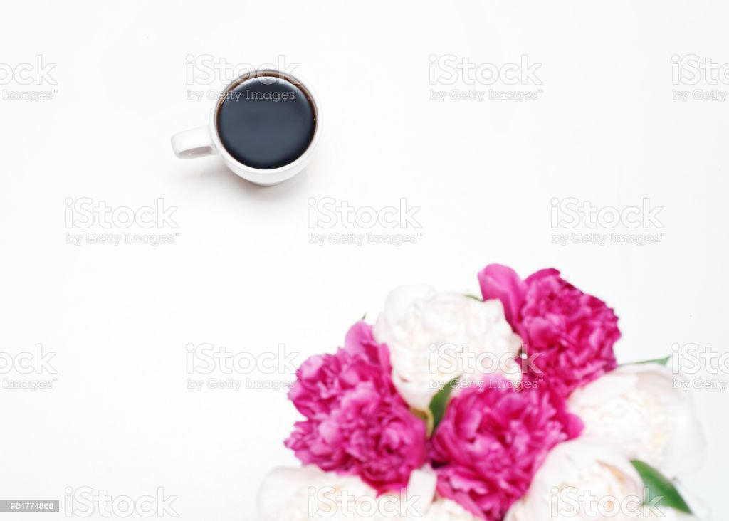 Work place with cup coffee white pink peony flowers royalty-free stock photo