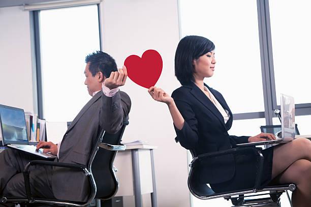 work romance between two business people holding a heart - flirten stockfoto's en -beelden