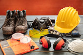 istock Work safety protection equipment. Industrial protective gear on wooden table, red color background. 1264334837