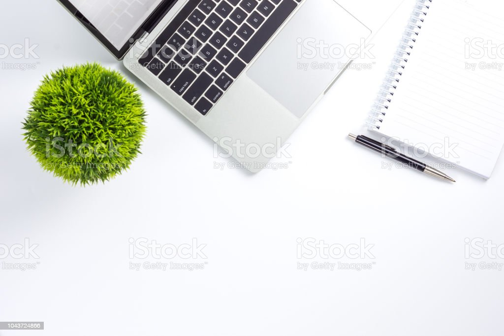 Work space on table with laptop computer, notebook, pen and plant...