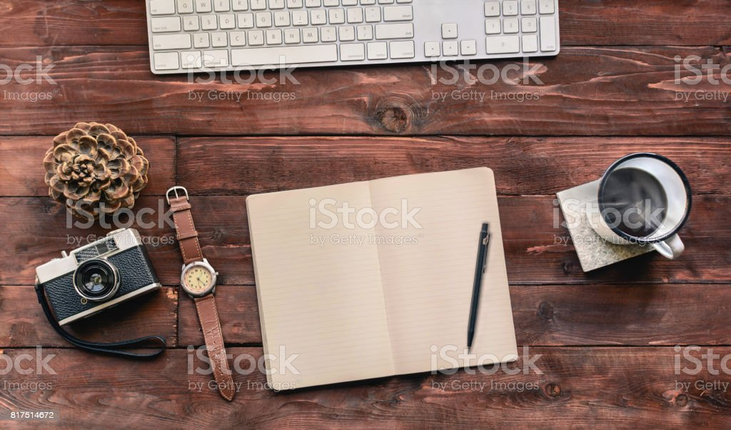 Work space on wood table of a creative designer or photographer with laptop, sketchbook, coffee and other objects of inspiration. Stylish home studio concept of technology trends. Vintage filter look stock photo