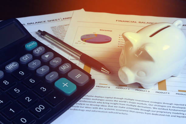 work station and coins and pig model on finance report , finance concept. - spending money stock photos and pictures