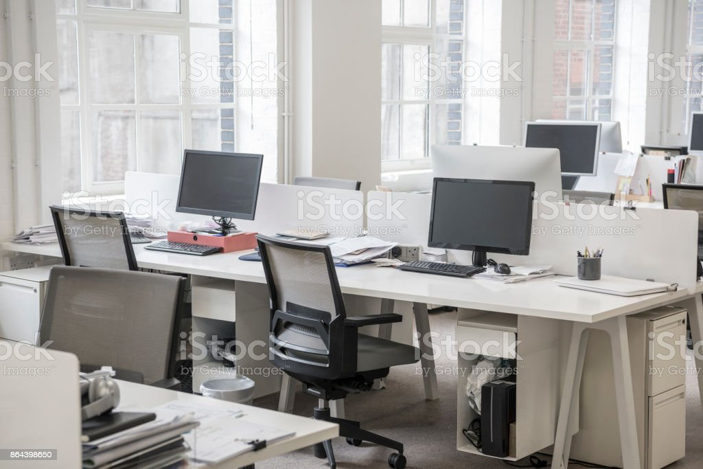 Modern office environment with desktop computers, stationery and...