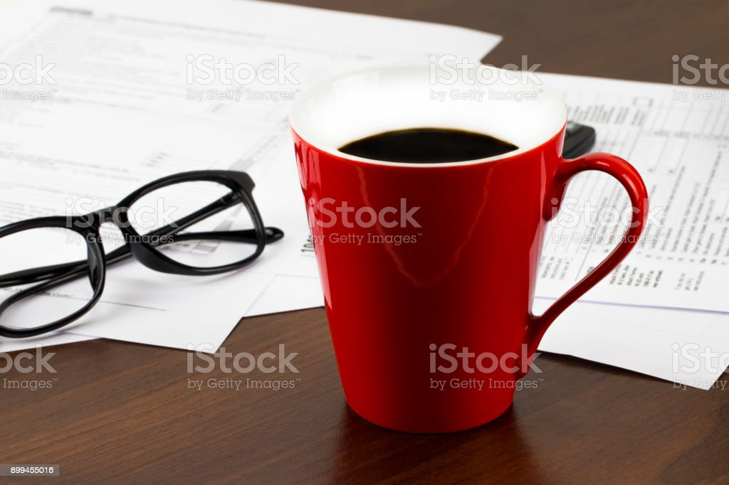 Work table covered with documents and a cup of coffee.