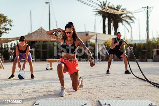 Young fit brunette doing lunges with a sandbag in an outdoor gym