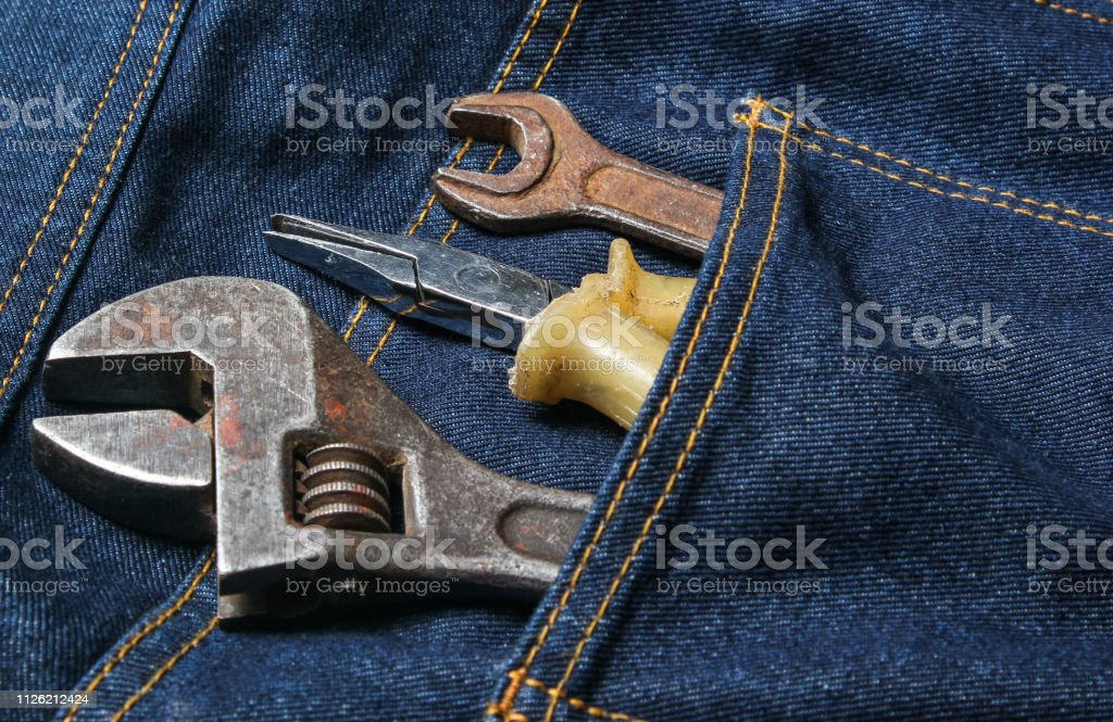 Work tool in the back pocket of the jeans. Pliers, wrench, adjustable...