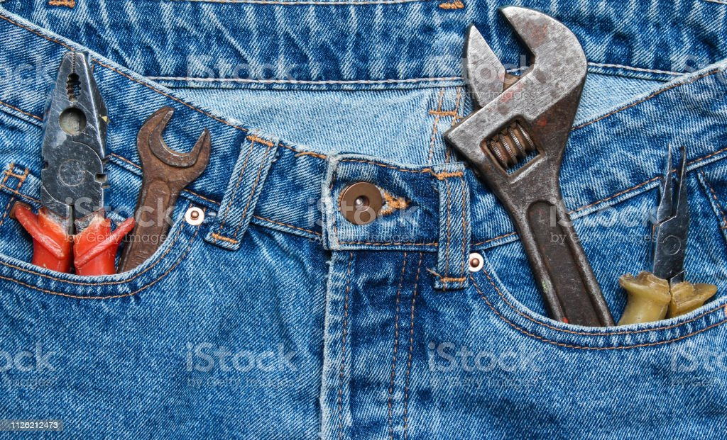 Work tool in the pocket of blue jeans. Pliers, wrench, adjustable...