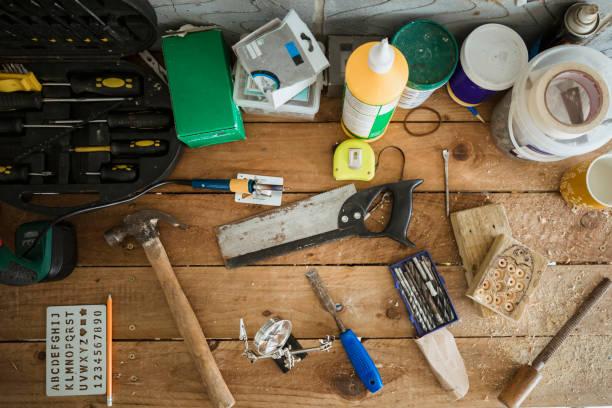 arbeitswerkzeuge auf einer holzwerkbank - werkzeugbank stock-fotos und bilder