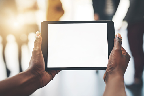 Shot of an unrecognizable man using a tablet inside